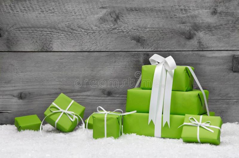 堆绿色圣诞节礼物,与在灰色的雪  免版税库存图片
