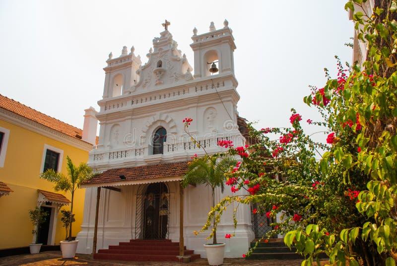 堡垒Tiracol 红色花背景的宽容大教堂  goa 印度 免版税库存图片