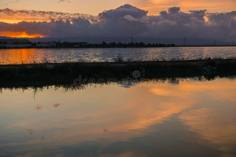 堤坝和池塘在日落的南旧金山湾,森尼韦尔,加利福尼亚 免版税库存照片