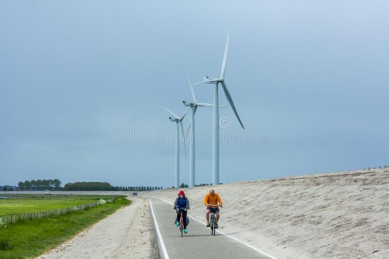 堤堰的骑自行车者与风轮机 免版税库存图片