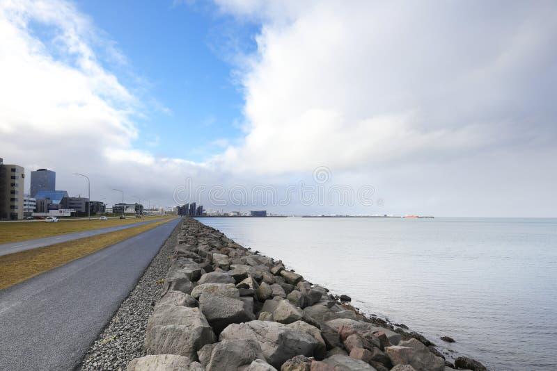 堤防在雷克雅未克,在海洋的日落在冰岛,戏曲 免版税库存图片
