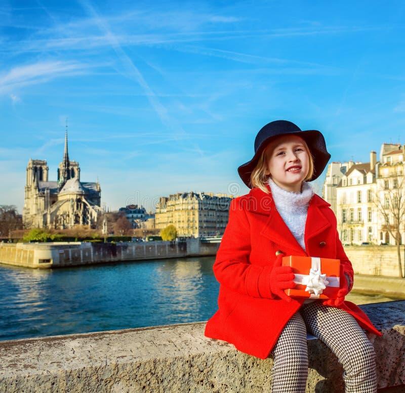 堤防的女孩在有圣诞节礼物的巴黎圣母院附近 免版税库存图片