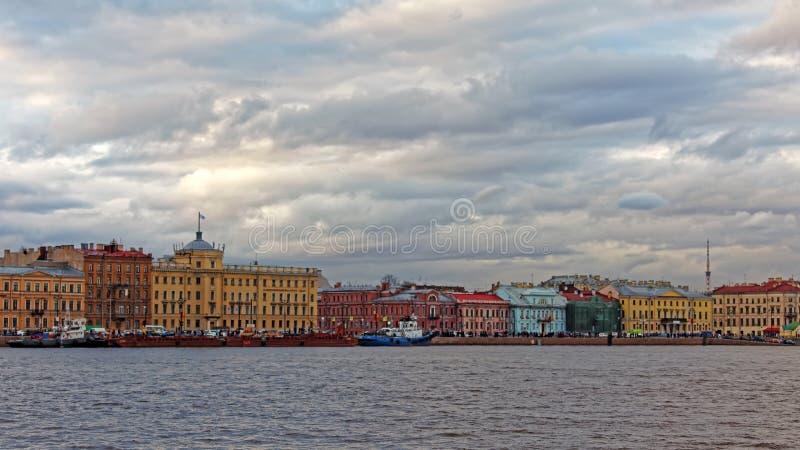 堤防都市风景视图在圣彼德堡,俄罗斯 艺术国子监  在日落的剧烈的都市风景 免版税库存照片