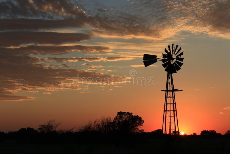 堪萨斯与橙色天空的风车剪影 库存图片