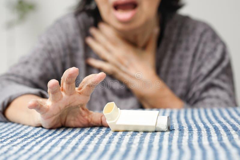堵塞和拿着哮喘浪花的年长妇女 库存图片