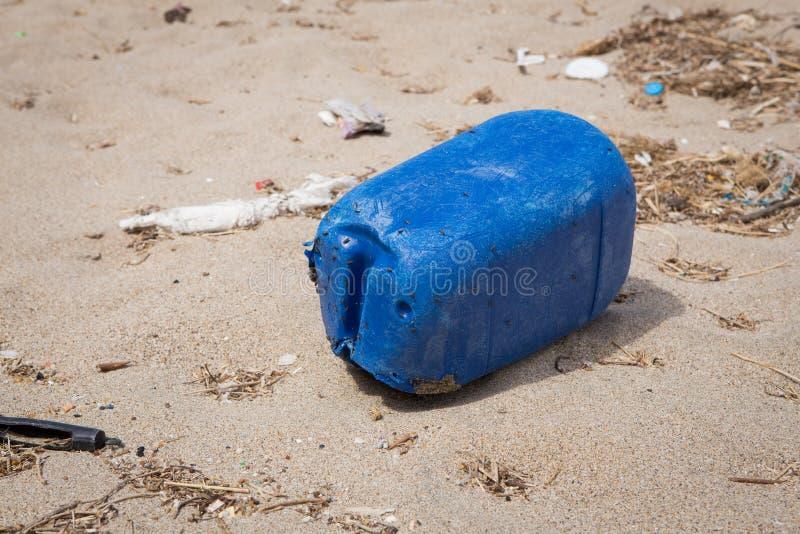 塑料五加仑装之汽油罐被冲上岸在海滩 库存照片