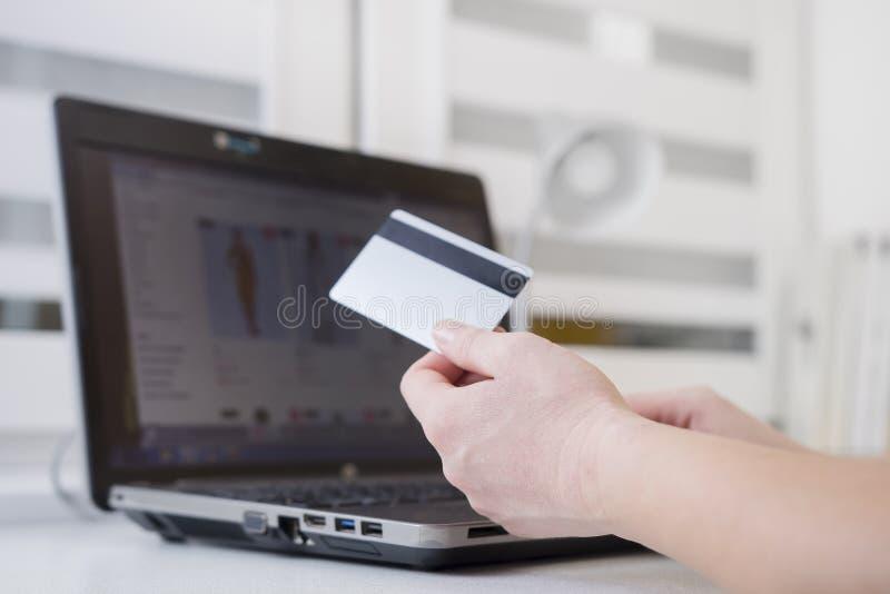 塑料信用卡在手中反对互联网编目的妇女在膝上型计算机显示  在线付款概念 免版税图库摄影