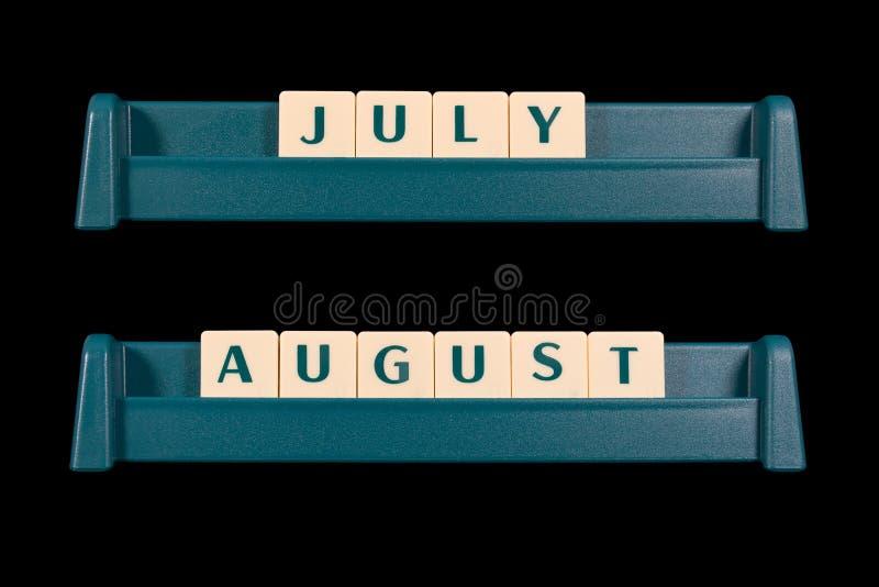 塑料信件瓦片 词包括7月和8月 免版税库存照片