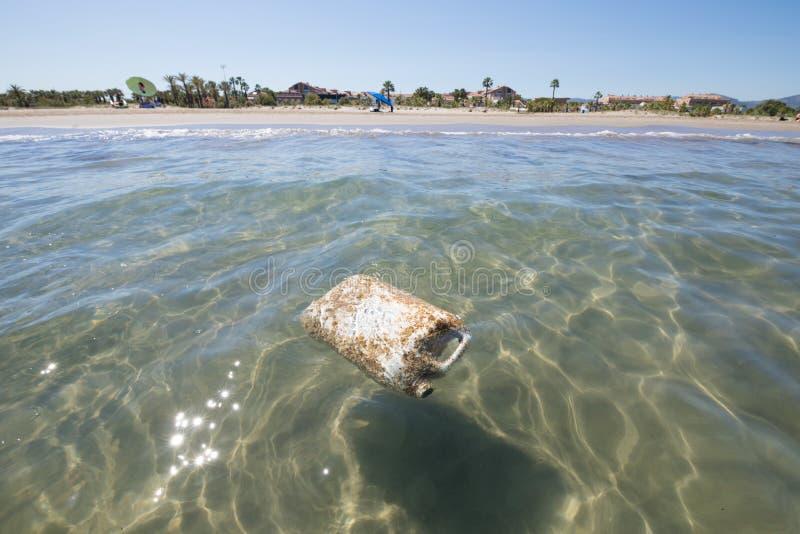 塑料储蓄在海滩旁边的海洋 免版税库存照片