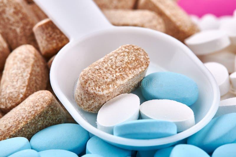 塑料匙子和蓝色,棕色和白色药片 免版税库存照片