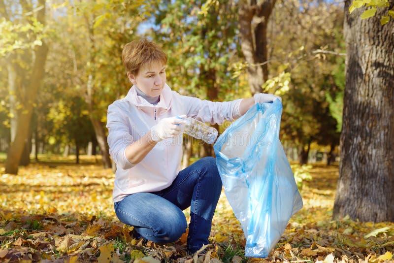 塑料垃圾的志愿采摘和投入它在生物可分解的垃圾袋子在户外 免版税库存照片