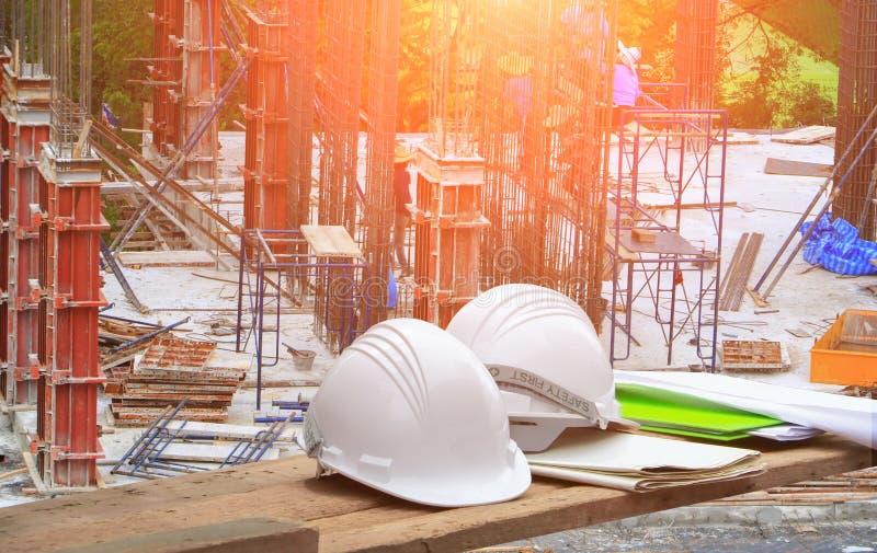 塑料安全帽和图纸在木头和工作者建筑在站点工作场所合作工作大楼商务有sunri的 图库摄影