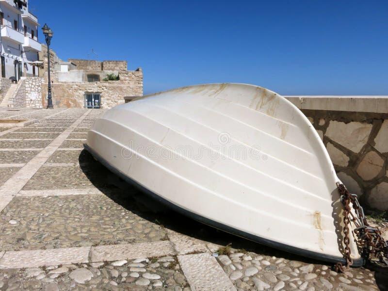 塑料小船说谎的底部在特拉帕尼被修补的街道  免版税库存图片