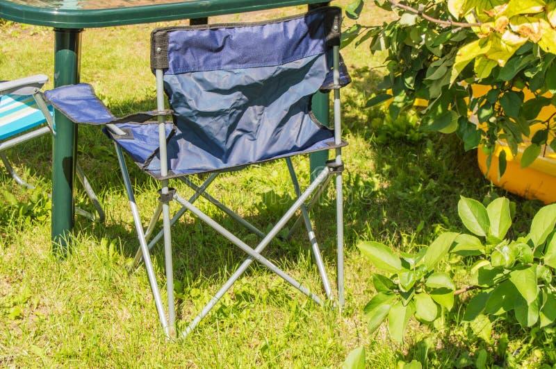 塑料折叠式小桌和折叠椅野营的立场的在草在一个晴朗的夏日 库存照片