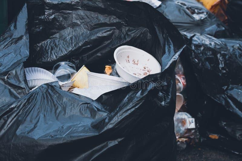 塑料杯子和泡沫在黑垃圾袋滚保龄球 免版税库存照片