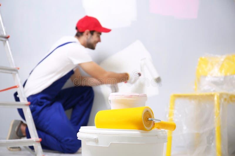 塑料桶和漆滚筒有被弄脏的工作者的 免版税库存图片