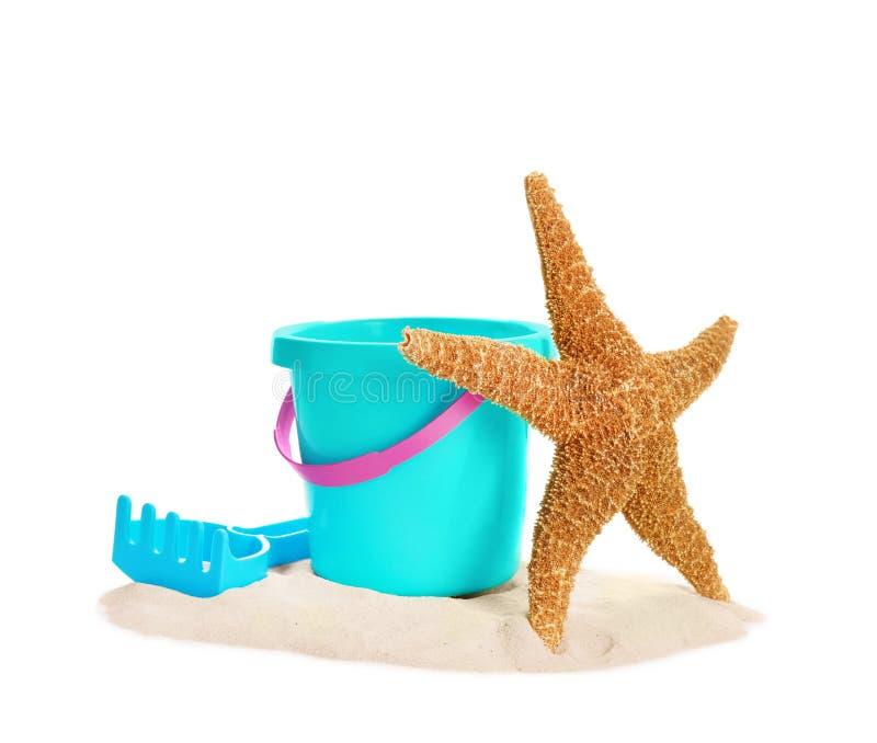 塑料海滩玩具和海星在堆沙子 免版税库存照片
