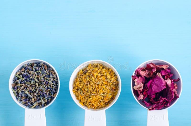塑料瓢用各种各样的医治草本-干燥万寿菊、淡紫色和狗玫瑰色花 芳香疗法,草药和自然 免版税库存照片