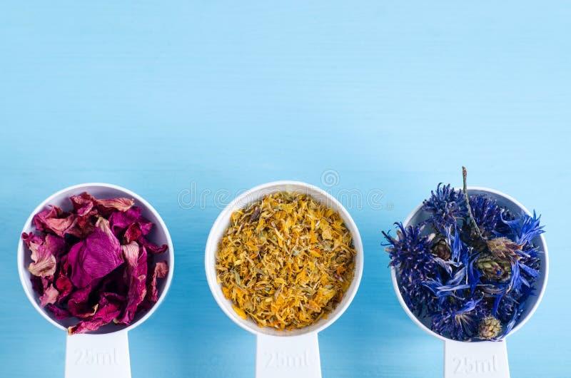 塑料瓢用各种各样的医治草本-干燥万寿菊、矢车菊和狗玫瑰色花 芳香疗法、草药和natur 免版税图库摄影