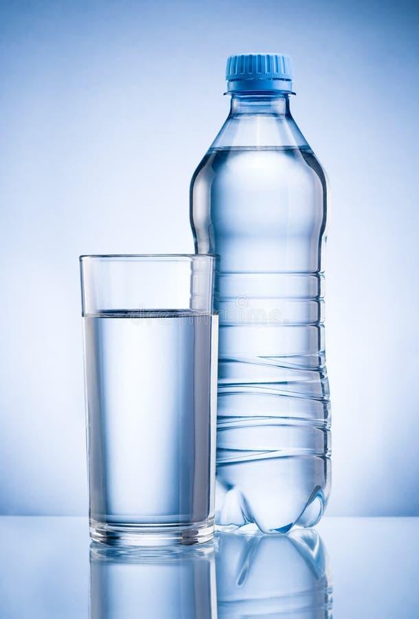 塑料瓶和杯在蓝色后面的饮用水 库存图片