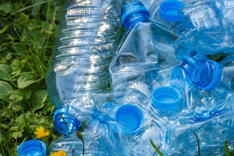 塑料瓶和瓶盖在草在公园,乱丢环境 免版税图库摄影