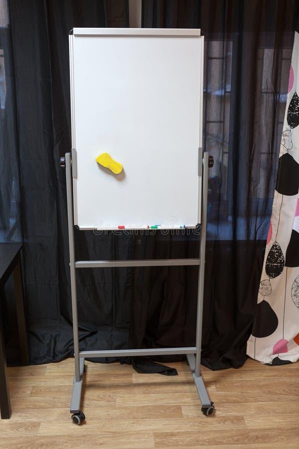 塑料白色flipchart在屋子内部,没人里站立 免版税图库摄影