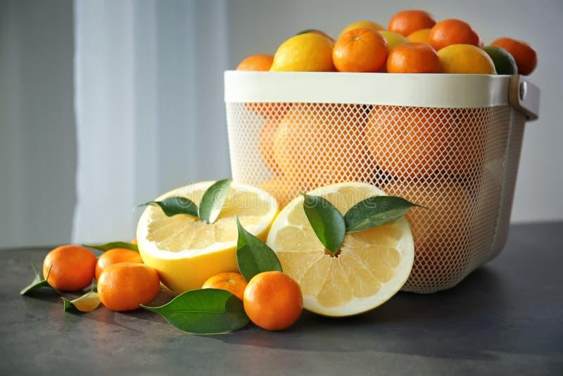 塑料篮子用新鲜的柑橘水果和一半 库存照片