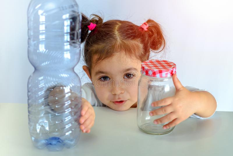 塑料自由,保存行星概念 推挤塑料瓶的孩子,拿着玻璃瓶子 反塑料竞选的图象 免版税库存图片