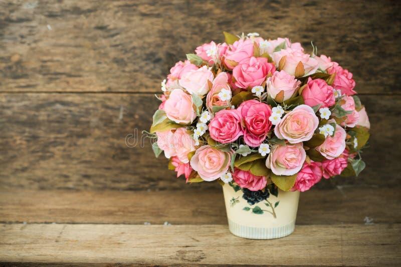 塑料花有在葡萄酒图片样式的木背景,家内部设备,花在木背景设置了 免版税库存图片