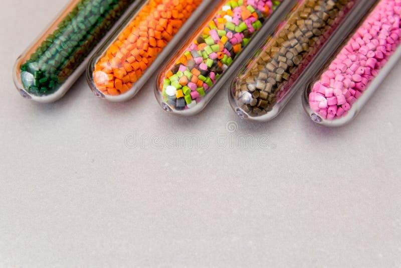 塑料药丸 在试管的聚合物染料在灰色背景 免版税库存照片