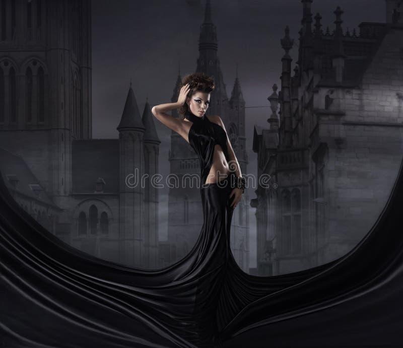 塑造一个少妇的射击黑色礼服的 免版税库存照片