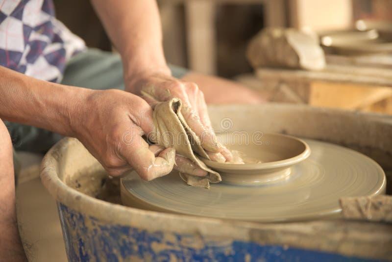 塑造一个灰色颜色黏土盘的老泰国男性手 免版税库存图片