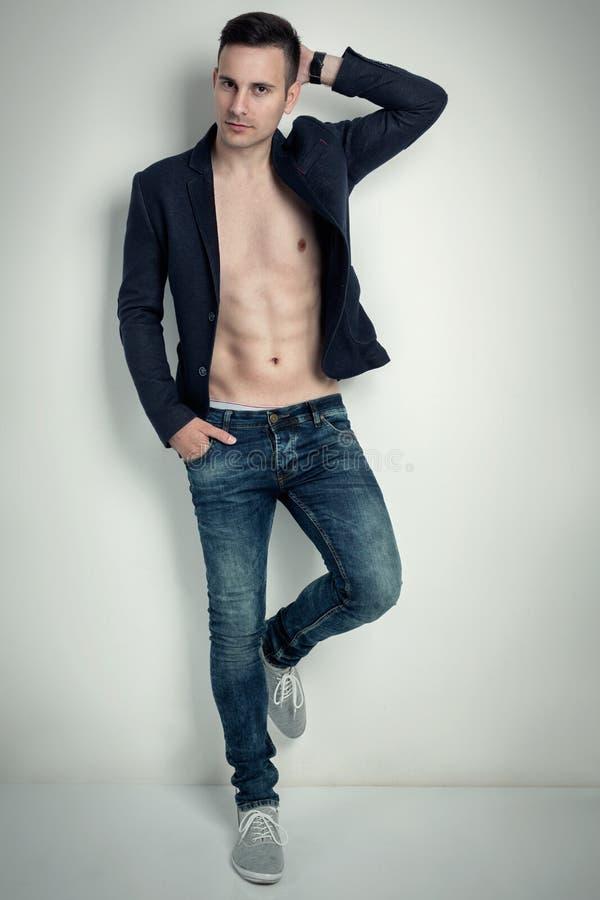 塑造一个热的男性模型的画象在时髦的牛仔裤的 免版税库存图片