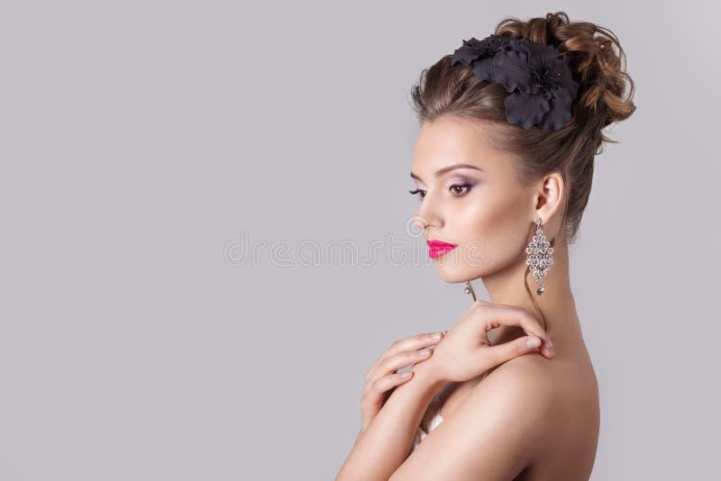 塑造一个美丽的可爱的女孩的画象有一个高柔和的典雅的晚上婚礼的发型和明亮的构成的 免版税库存照片