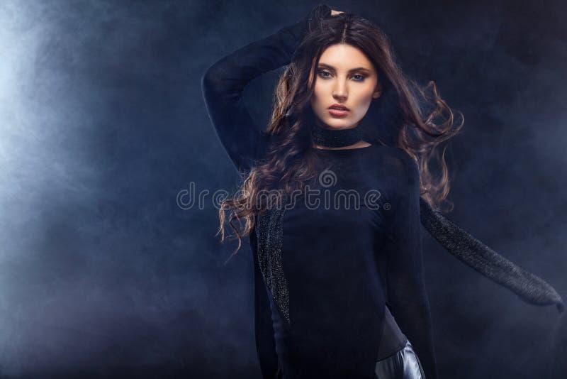塑造一个美丽的少妇的照片摆在与烟的黑背景的一件俏丽的礼服的 时尚照片与 免版税库存图片