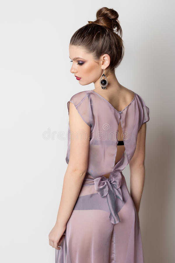 塑造一个年轻美丽的女孩的画象一件轻的透明礼服的有一种明亮的晚上构成和发型的 免版税库存图片