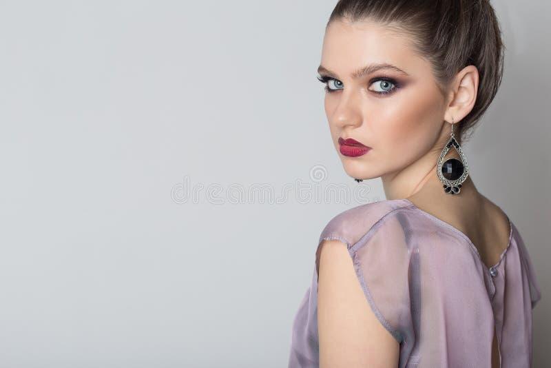 塑造一个年轻美丽的女孩的画象一件轻的透明礼服的有一种明亮的晚上构成和发型的 库存图片