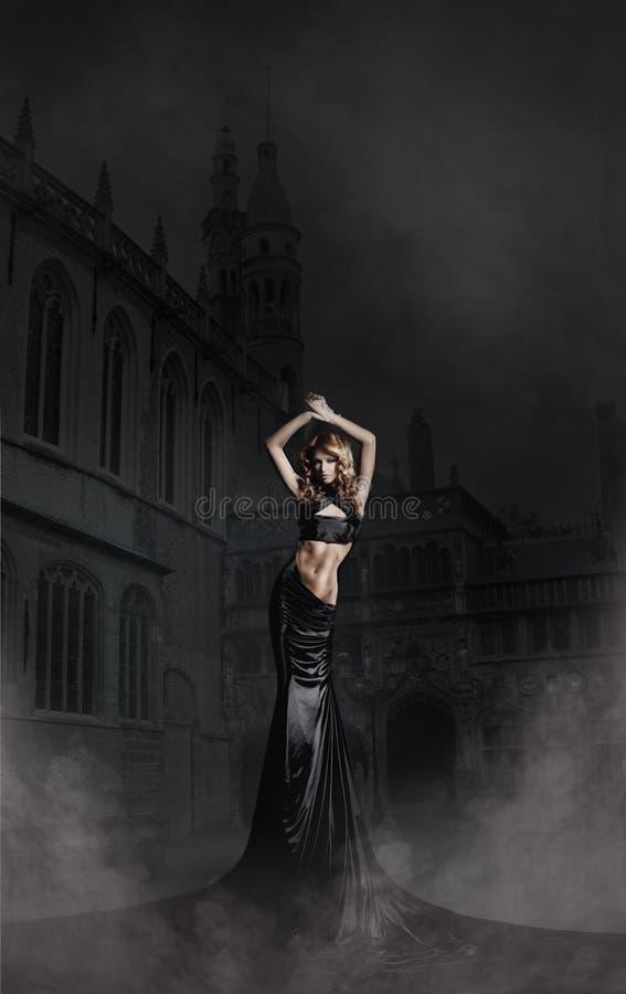 塑造一名妇女的射击一件长的黑色礼服的 库存图片