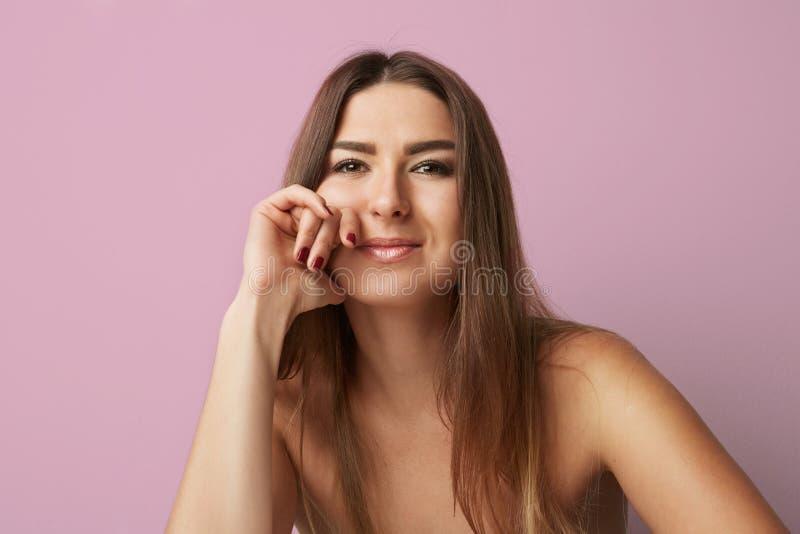 塑造一名美丽的微笑的妇女的画象有长的头发的在空的桃红色背景 床单方式放置照片诱人的白人妇女年轻人 水平 免版税库存图片
