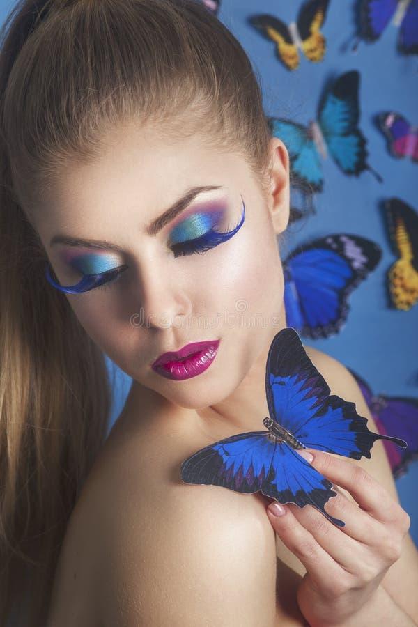 塑造与一只蝴蝶的秀丽Gir在她的handl 华美的纵向妇女 发型 组成 时髦样式 背景黑色女孩魅力例证 免版税库存图片
