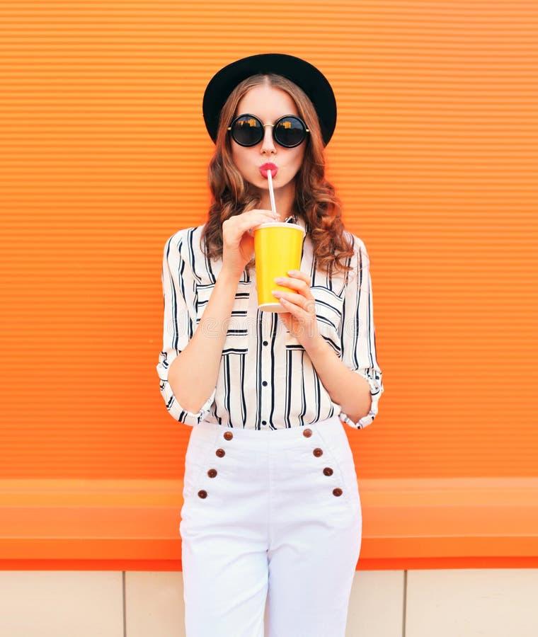 塑造与新鲜水果穿在五颜六色的桔子的汁杯子的俏丽的妇女模型黑帽会议白色裤子 免版税库存照片