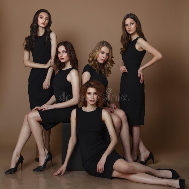 塑造五名elgant妇女演播室照片黑礼服的 免版税库存照片