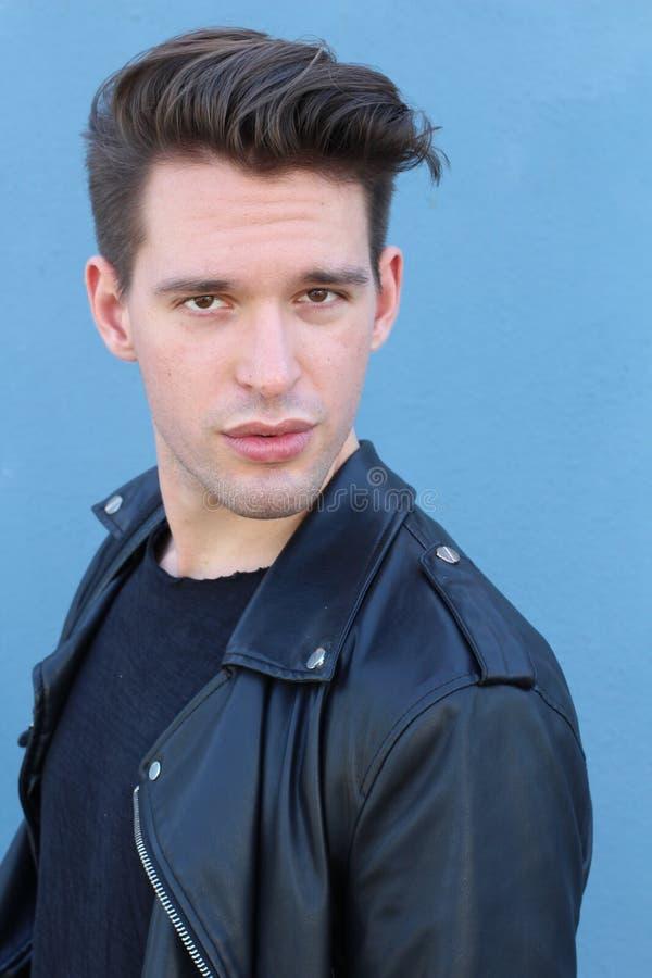 塑造人,英俊的严肃的秀丽男性式样画象佩带的皮夹克,在蓝色背景的年轻人 免版税库存照片