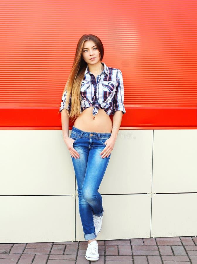 塑造佩带一方格衬衣和牛仔裤摆在的俏丽的妇女 免版税库存照片