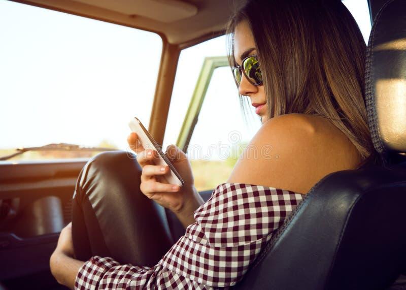 塑造使用她的手机的美丽的女孩在汽车 库存照片