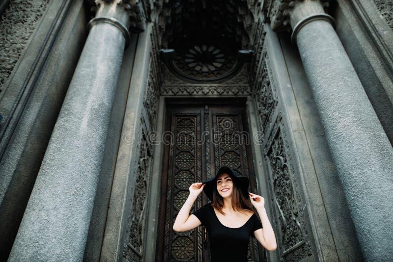 塑造出现的逗人喜爱的女孩摆在反对巨大的美丽的门背景在黑礼服和帽子的 库存照片