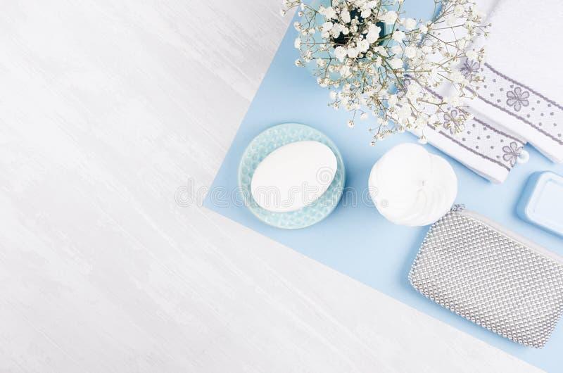 塑造化妆产品集-白色肥皂,毛巾,花,肥皂分配器,蓝色陶瓷花瓶,在蓝纸的银色化妆袋子 免版税图库摄影