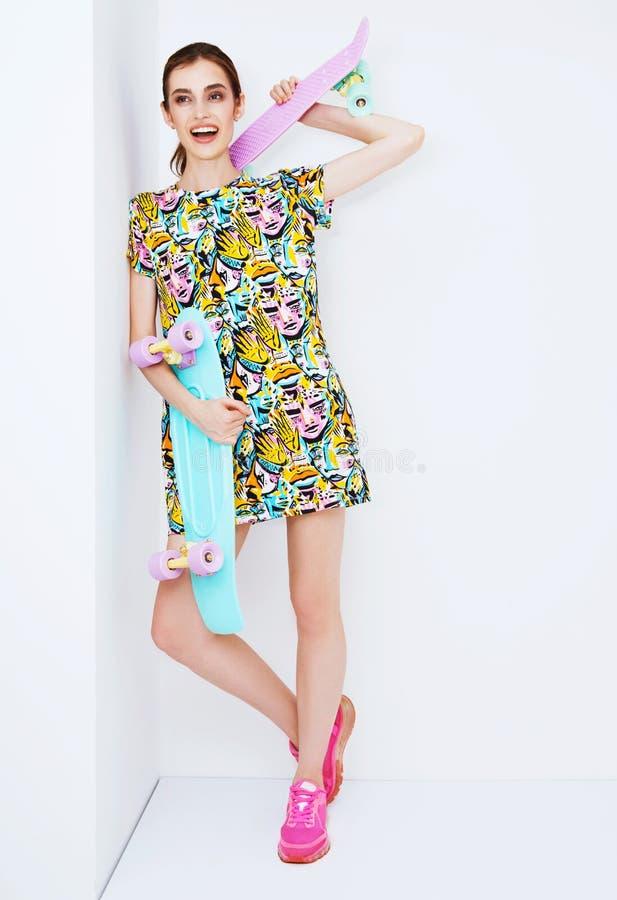 塑造在五颜六色的礼服的性感的时髦模型与 图库摄影