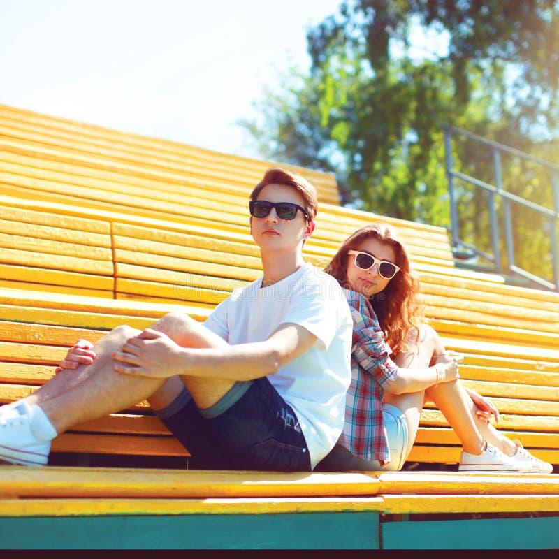 塑造在太阳镜的年轻的夫妇坐长凳 库存照片