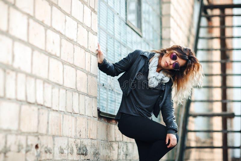 塑造在太阳镜,黑色皮夹克,牛仔裤 摆在红砖墙壁附近 库存照片